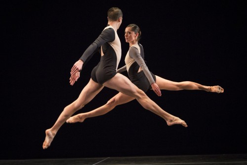 A male and female dancer suspend in the air,  caught in a moment of jumping.