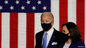 An image of Joe Biden and Kamala Harris standing next to one another. They wear masks and stand in front of a large American Flag. The text