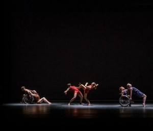 Three pairs of dancers are in a beam of light on a black stage; in each pair, one dancer leans on another, and two dancers are wheelchair users