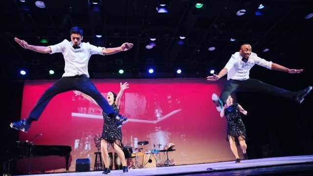 Tap dancers leap enthusiastically in a straddle position on stage
