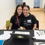 two dance/NYC volunteers posing for a photo at the legal clinic registration table from Dance/NYC 2018 Symposium