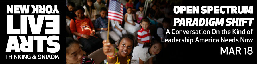 A young girl of color perhaps in the age range of 5 through 8 in a bright yellow dress holds a small American flag above her head and looks at it in a hopeful way.