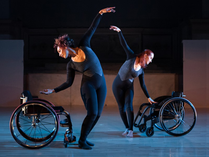 Two dancers wearing black and grey bodysuits, standing beside two wheelchairs side by side on a blue lighted floor.