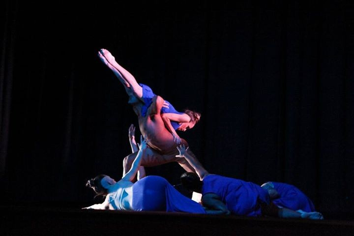 A female dancer being lifted in the air by a male dancer while being surrounded by various dancers