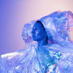 A performer in profile wears a voluminous, iridescent headpiece and blouse and is cast in a purple glow.