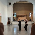 Performers are moving in front of an old gymnasium stage. The floor is grey and the walls are white.