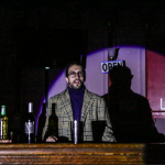 a bespectacled man behind a bar