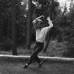 A black & white photo of Douglas Dunn dancing in forest in 1983