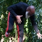 Raphael is wearing a black sweat suit with red stripes. He is bent over at the hips, knees bent with arms reaching out.