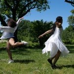Two dancers dressed in white are captured mid-spin, their feet skimming the grassy field