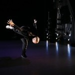 A dancer wearing all black in a black box theater falling towards the ground with one leg on the floor with the other in the air