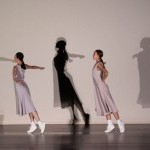 Two women in basic light grey dresses in their dance positions with the shadows projected behind them.