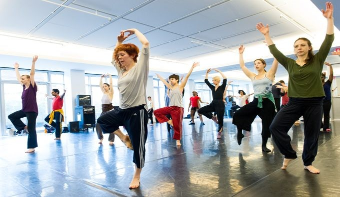 Approximately 10 dancers in a studio working on basic ballet movement
