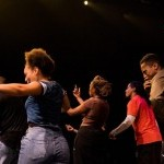 Five people of color on stage dancing in a celebratory fashion
