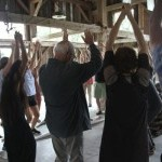 A large group of people in a barn with light trickling in as the participants cast their arms up in the air.