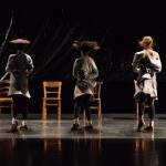 Three dancers is muted colors like a soft grey and black, turning in motion with wooden chairs behind them.