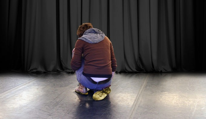 A person in a brown hoodie and blue jeans turned with their back towards us, with back hunched over crossed knees.