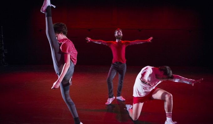 Three dancers on a dark stage with red lighting on different levels and positions