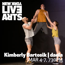 Three performers in a blackbox, two of them lifting the performer in the middle who is looking backwards.