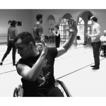 A dancer in a wheelchair looking down over his shoulder with arms uplifted towards his other shoulder.