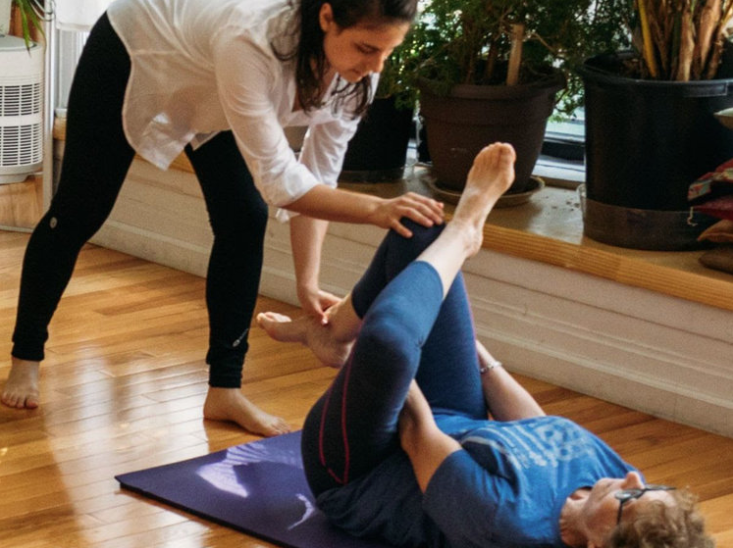 A student is laying on the floor in a figure four stretch while an Alexander Technique teacher assists with hands on.