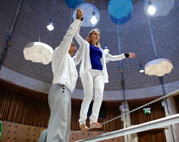 Photo of a woman in white clothing walking on a tightrope with the assistance of the teacher who is lightly helping her balance.
