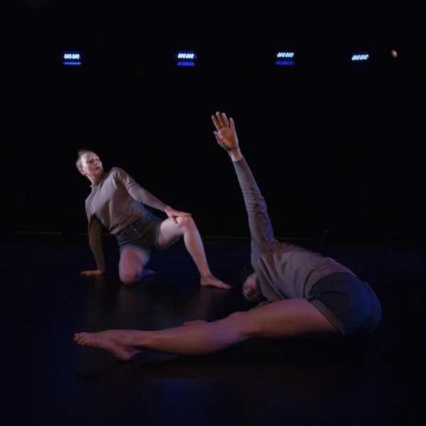 Garnet Henderson and Rebecca Hadley dancing, low to the ground, dimly lit