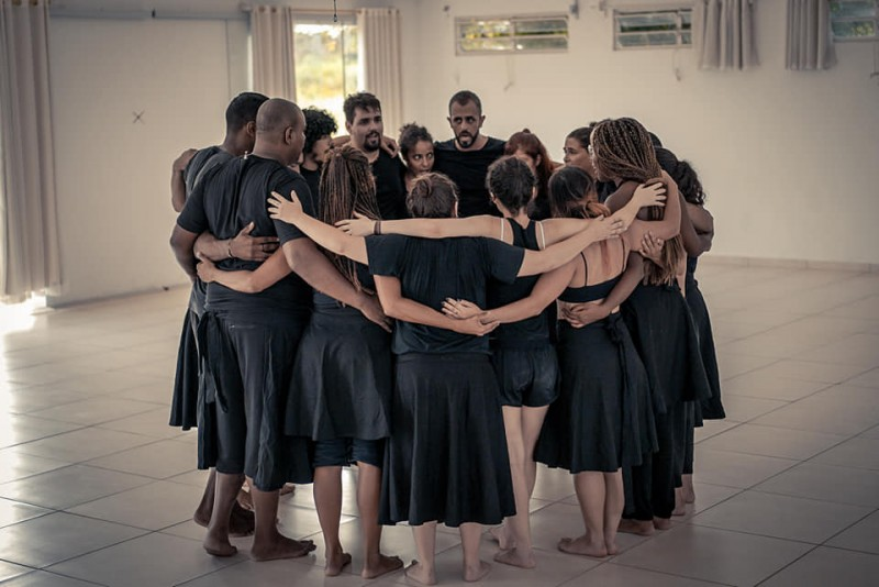 A group of people are gathered in a circle facing each other with their arms embracing each others' shoulders