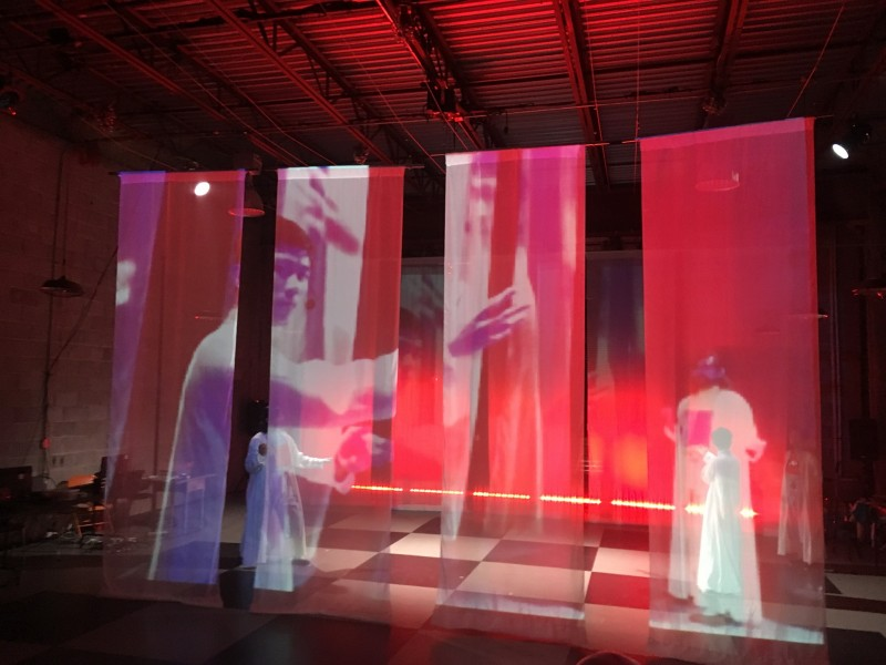 projection of kung fu movie on silk hangings while dancer moves below. red lighting on stage.