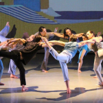 "Group photo of Alison Cook-Beatty's dance, ""Whale."" Circular formation of dancers interlocking arms and balancing in a stag."