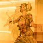 an triple image of a woman with a traditional odissi costume on in a gallery space near the sculptue 0+0=0-0 by Tallur L.N.