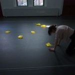 Female dancer on hands and knees, surrounded by squares of folded thin yellow plastic, in a studio with light from windows