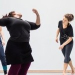 Alexandra Beller Spiraling in a dance studio, looking back at students who look on spiraling on their own.