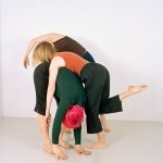 Three dancers fold on top of each other. One dancer has bright pink hair