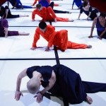 12 figures lay on the floor in nearly identical poses, both hands flat, right leg outstretched and left leg crossed over