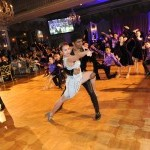 Two people dancing as partners on a ballroom floor.