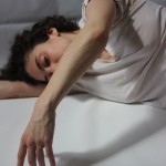 Person in white tee-shirt lies on her right arm on her side tracing the floor with the fingertips of her left hand