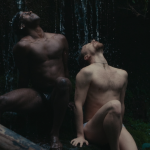 Two dancers with gazes extended upwards sit while barechested