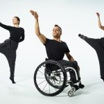 a photo of 3 dancers, one in a wheelchair, 2 jumping in the air. All 3 dancers have 1 arm in the air