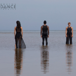 Three dancers facing front and back standing on the beach at low tide.