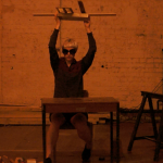 Woman sitting at a table and lifting objects overhead.