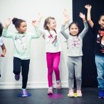 diverse group of children jumping in hip hop class