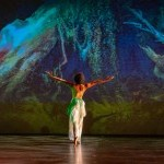 female dancer in white facing green/blue projection of roots of trees