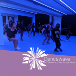 People dancing in an blue-lit studio with the Dancewave logo superimposed