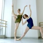 Two women dancers posing.  One in a green leotard and her leg extended to the side.  The other in a blue leotard in a lunge.