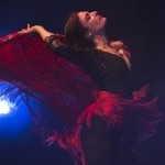 A female flamenco dancer with her head tilted back, flinging a maroon shawl