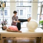 One body laying on a Pilates Cadillac with instructor assisting