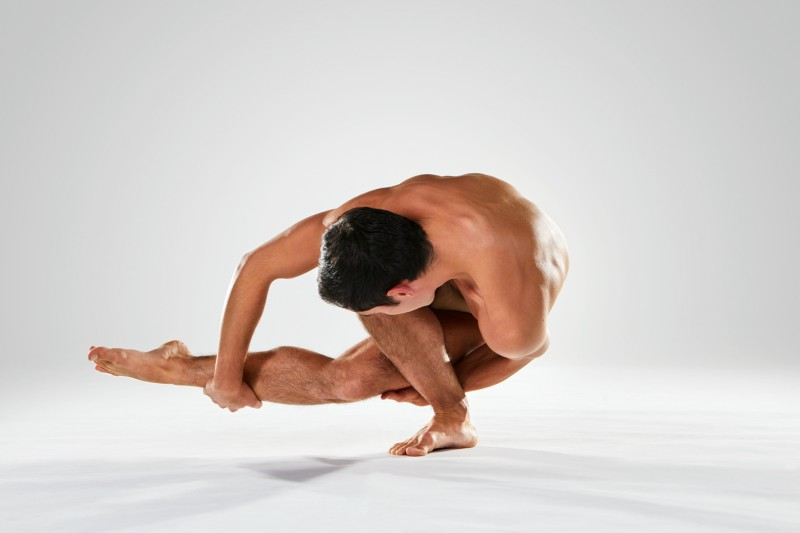 Male dancer twisting low and touching foot