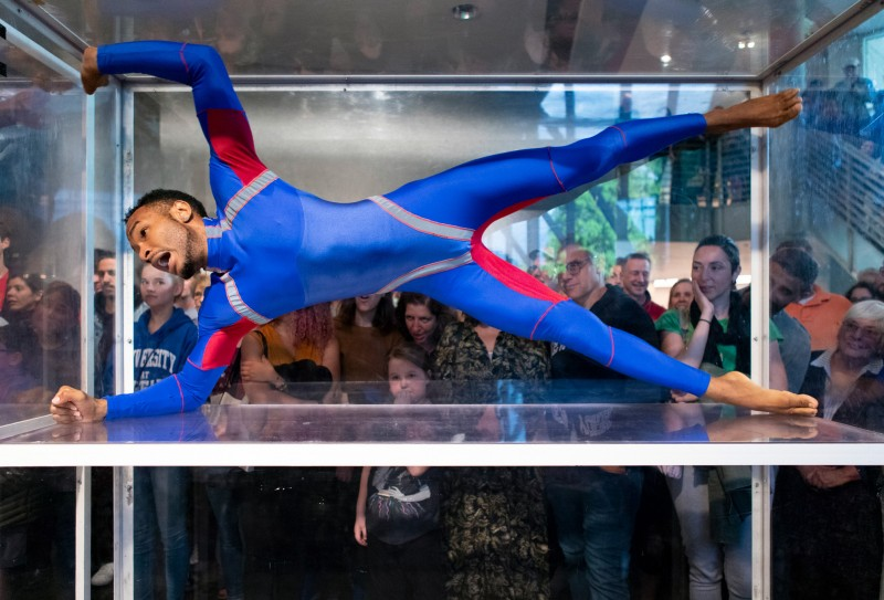 Man in blue unitard making a side X shape in a clear box