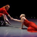Dancer Kitty Lunn, who uses a wheelchair, and dancer Alison Cook each has one arm outstretched and they grasp hands.